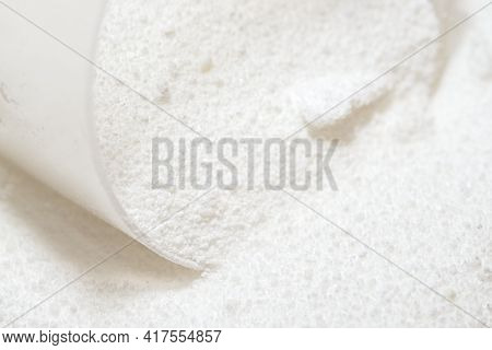 Macro Image Of Clear Plastic Scoop Measuring Out White Laundry Detergent Powder. Domestic Cleaning C