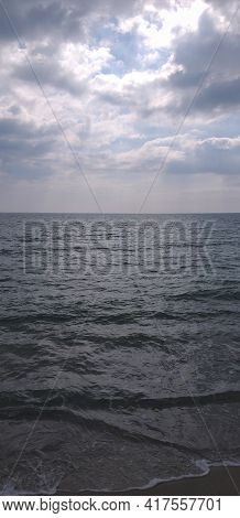 Vertical Background: Waves Rolling On The Shore, Blue Sky With Clouds