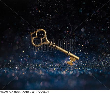 Single golden skeleton key surrounded by sparkling lights. Business concepts of unlocking potential, key to success, or financial opportunity.