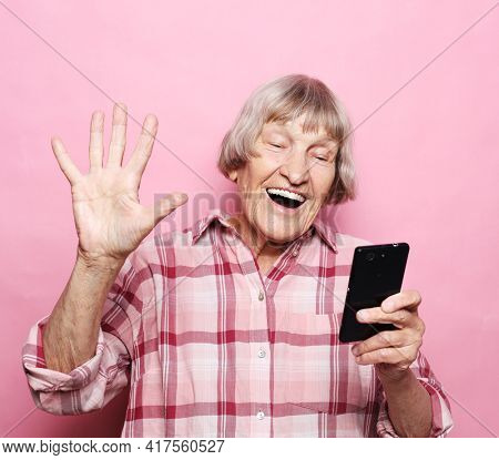 Lifestyle, tehnology and old people concept: Image of cheerful mature elderly woman with mobile phone.