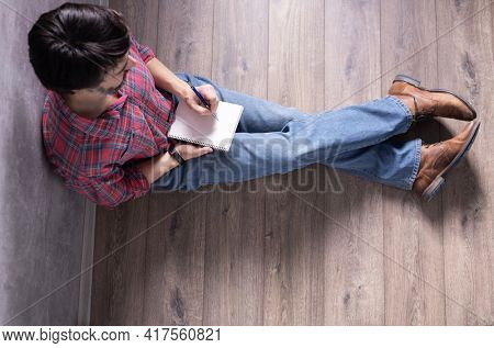 Man sitting on floor and holding pencil or pen with notebook. Student writing by pen or drawing by pencil in sketchbook. Study designer concept