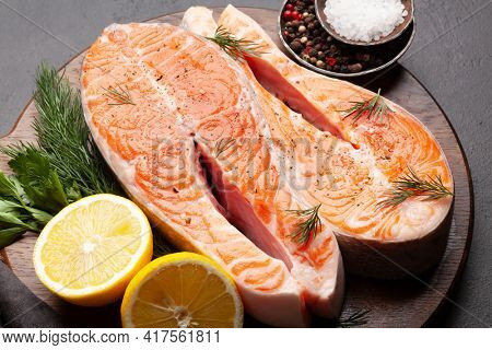 Fresh raw salmon cooking. Fish steaks with herbs and spices on cutting board