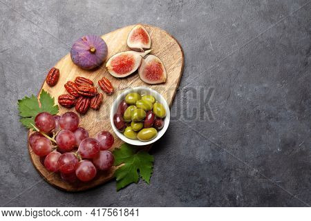 Antipasto plate with nuts, figs and grapes. Appetizer board. Top view flat lay with copy space