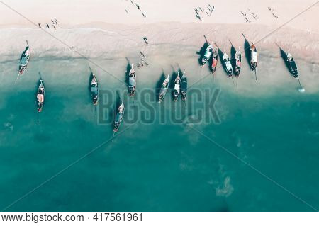 Aerial, drone view of a beautiful tropical beach with white sand, turquoise clear water and longtail boats near Krabi, Thailand.