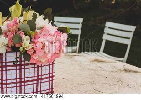 Flowers in gift box outside on table with text space
