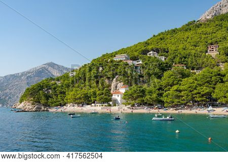 Makarska, Croatia - September 5, 2019: Beautiful beach at Adriatic Sea in Makarska Riviera, Dalmatia, Croatia. Unidentified people enjoy beach holidays in Croatia