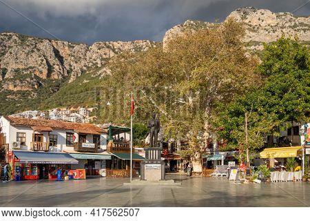 Kas, Turkey - December 2, 2020: Main square of the mediterranean town Kas in Turkey. Statue of Mustafa Kemal Ataturk, founder of Turkish Republic in the middle