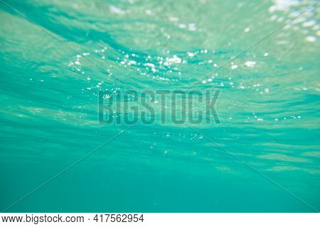 Turquoise calm sea with waves and rays of sunlight shining through, underwater. Ocean. Tranquility and silence. Beautiful natural background, wallpaper