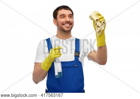 profession, cleaning service and people concept - happy smiling male worker or cleaner in overall and gloves with rag and detergent over white background