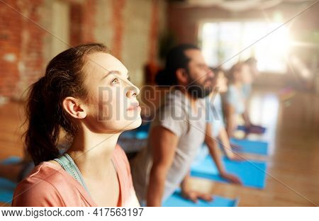 fitness, yoga and healthy lifestyle concept - woman with group of people doing cobra pose on mats at studio