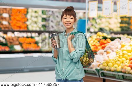 sustainability and people concept - portrait of happy asian woman in turquoise shirt with thermo cup or tumbler for hot drinks over grocery store background