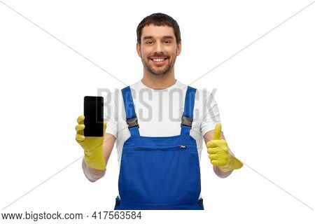 profession, cleaning service and people concept - happy smiling male worker or cleaner in overall and gloves showing smartphone showing thumbs up over white background