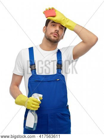 profession, cleaning service and people concept - tired male worker or cleaner in overall and gloves with sponge and detergent over white background
