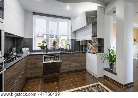 Modern luxurious dark brown, gray and black kitchen interior, dishwasher door is open