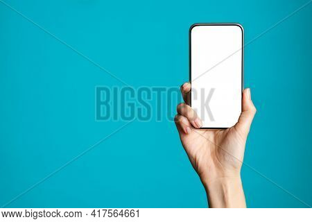 Woman hand holding smartphone with blank screen isolated on blue background. Close up of hand showing cellphone isolated against azure wall with copy space. Phone with empty screen ready for your app.