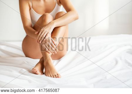 Detail of beautiful young woman hands and legs with perfect smooth soft skin after beauty treatment sitting on bed with copy space. Laser epilation, cosmetology, spa, and hair removal concept.