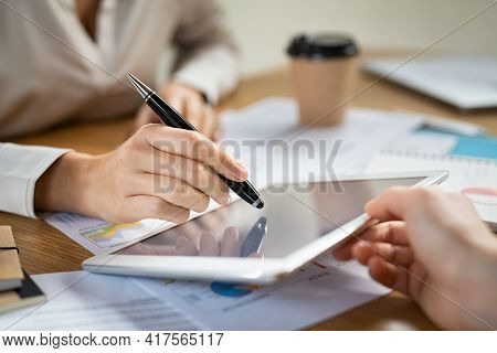 Digital signature on tablet. Close up of hand of young businesswoman signing documents on digital tablet with pen. Business woman hand pointing digital tablet with pen while working at desk.