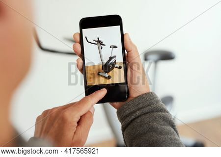 closeup of a young caucasian man taking a picture, with his smartphone, of a stationary bicycle to sell it on an online marketplace app to sell and buy secondhand goods