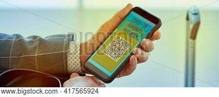 closeup of a young businessman having a simulated electronic covid-19 immunity passport in his smartphone, in the waiting hall of an airport, in a panoramic format to use as web banner or header