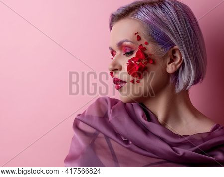 Stylish And Bright Young Woman With Colored Makeup And Flower Petals On Her Face