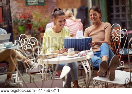 Two female students enjoying an interesting book while have a drink on a beautiful day in bar's garden. Leisure, bar, friendship, outdoor