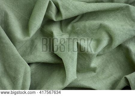 Green Crumpled Fabric Texture Background. Close Up.