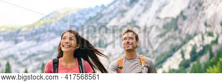 Hikers couple hiking happy in mountains landscape panoramic. Smiling Asian woman, Caucasian man multiethnic group campers with backpacks. Camping summer travel banner background.
