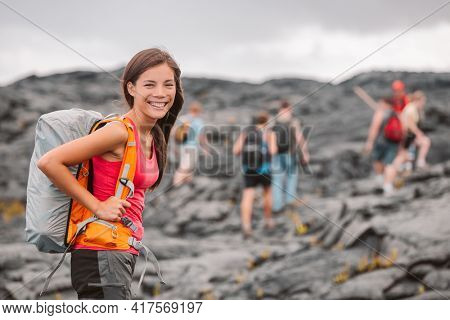 Hawaii volcano hike adventure happy Asian woman with backpack in Big Island, Hawaii. Hiking group of tourists walking on black lava field trail. Smiling Asian girl outdoor USA summer travel vacation.