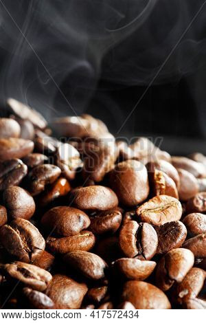 Hot roasted coffee beans and steam on black background with copy space