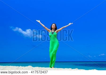 Happy smiling woman enjoy vacation on beach with raised hands
