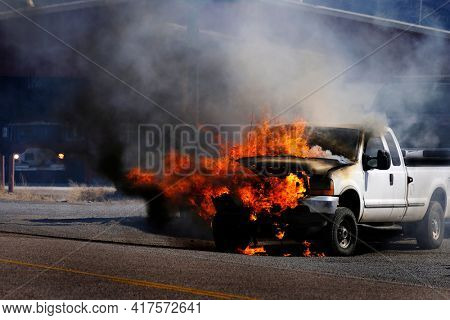 Truck vehicle on fire burning in flames billowing smoke destroyed on roadway