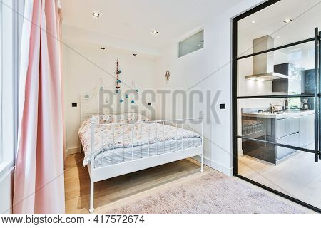 Comfortable Bed With Warm Duvet Located In Cozy Bedroom Near Glass Door Leading To Kitchen