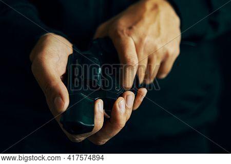 Mens Hands Check For Bullets In Revolver Barrel. Reloading Gun Close-up. Guy Prepares Pistol For Sho