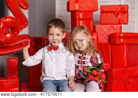 Pretty Little Girl And Boy Celebrating Saint Valentine Day. Little Boy Giving A Red Flower To A Beau