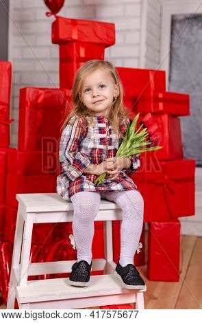 Charming Girl Holds A Bouquet Of Tulips. Young Blond Girl Celebrating Her Birthday At Home. Portrait