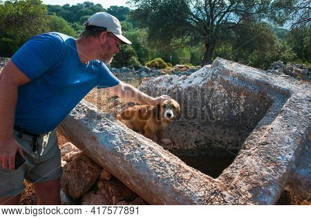 Man is petting a dog on ancient rock tomb ruins along the Lycian way hiking trail, Trekking in Turkey, outdoor activity
