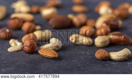 Assortment Of Various Types Of Nuts On Dark Background. Cashew, Hazelnuts, Almonds And Brazil Nuts C