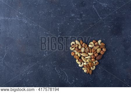 Heart From Various Types Of Nuts On Dark Background. Cashew, Hazelnuts, Almonds And Brazil Nuts Top