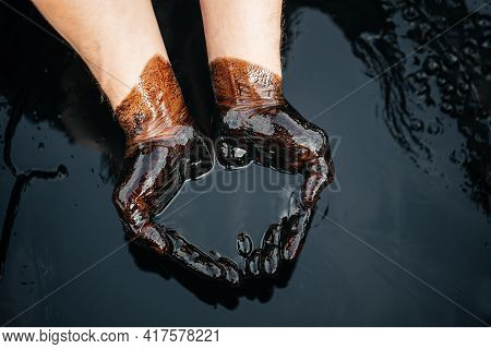 Caucasian Oil Hands Are Folded In A Bowl Of Oil. Oil Spill. Environmental Pollution. An Environmenta
