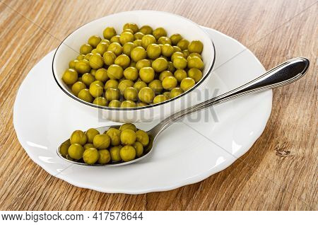 White Glass Bowl With Canned Green Peas, Metallic Spoon With Green Peas In Plate On Brown Wooden Tab