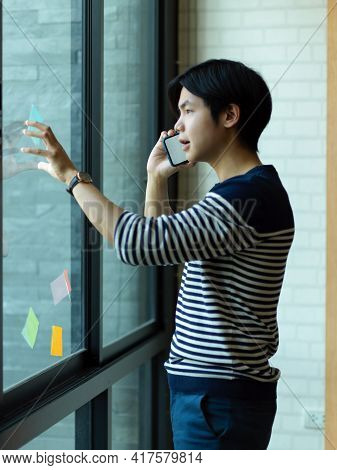 Businessman Talking On The Phone While Reading An Idea On Sticky Note On Glass Wall In Office