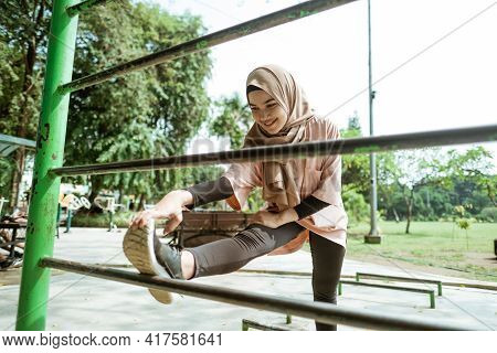 A Beautiful Girl In A Veil Does Leg Stretches Over An Iron Bar
