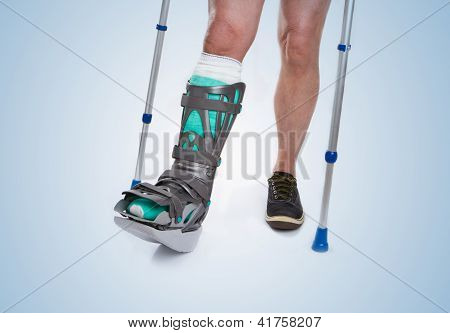 Man With A Broken Leg With Crutches On A Blue Background