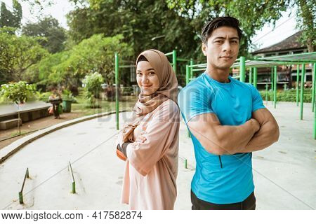 A Young Man And A Girl In A Veil Stand Back To Back With Crossed Hands