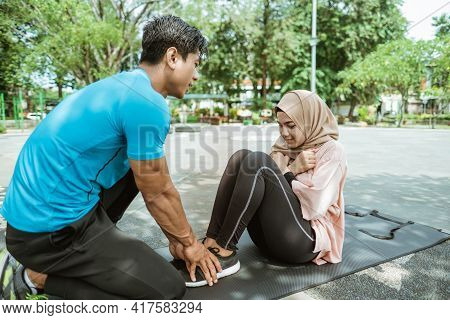 A Young Man Helps Hold The Legs Of A Veiled Girl Doing Abs Workouts During Outdoor Sports