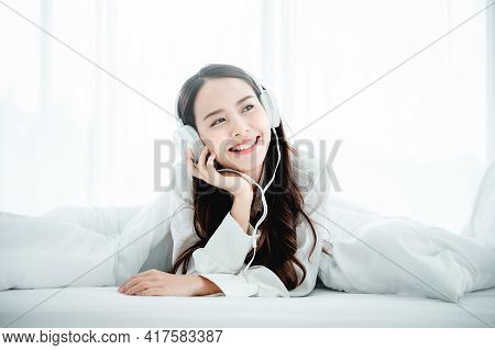 Beautiful Young Asian Woman In Headphones Listening To Music And Lying Down On Bed At Bedroom In Mor