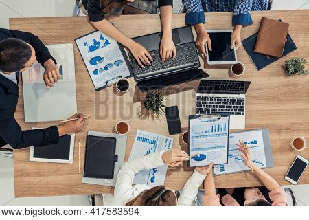 Top View Of Businessman Executive In Group Meeting With Other Businessmen And Businesswomen In Moder