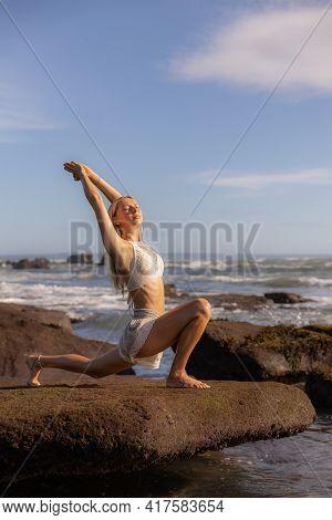 Bali Beach Yoga. Slim Woman Practicing Ashwa Sanchalanasana, Equestrian Pose. Fit Body. Healthy Life
