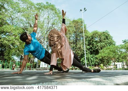 A Man And A Girl In A Veil In Gym Clothes Doing Hand Exercises Together For Endurance Training