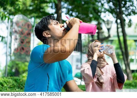 A Muscular Man And A Girl In A Veil Drinking With A Bottle Out Of Thirst During Their Outdoor Sports